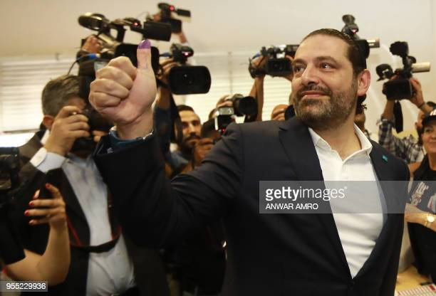 Lebanese Prime Minister Saad Hariri gives a thumbsup with his inkstained thumb after voting at a polling station in the capital Beirut on May 6 2018...