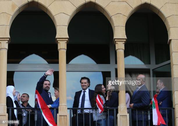 Lebanese prime minister Saad Hariri greets his supporters in the presence of Lebanese singer Ragheb Alama upon his arrival at his home in Beirut on...
