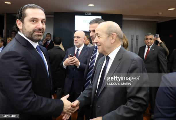 Lebanese Prime Minister Saad Hariri shakes hands with French Foreign Affairs Minister JeanYves Le Drian as they attend the Cedre conference at The...