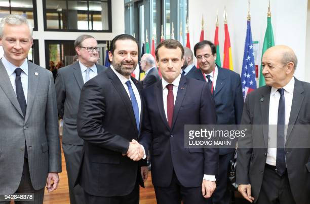 Lebanese Prime Minister Saad Hariri shakes hands with French President Emmanuel Macron flanked by French Economy Minister Bruno Le Maire and French...