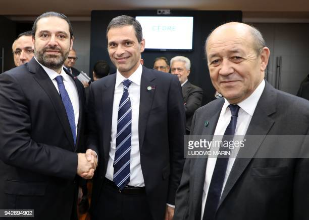 Lebanese Prime Minister Saad Hariri shakes hands with general managing director of CMA CGM group Rodolphe Saade as French Foreign Affairs Minister...