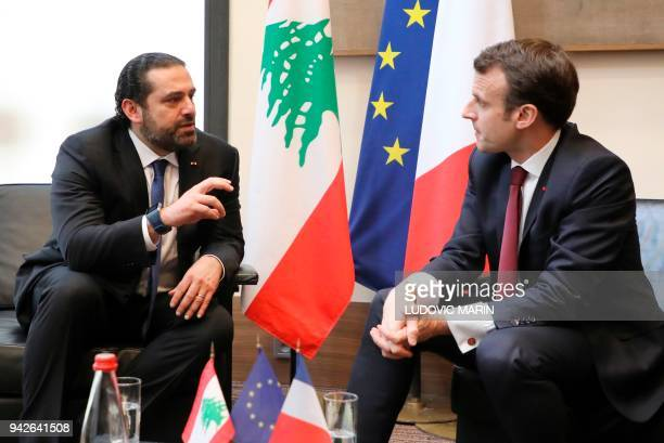 Lebanese Prime Minister Saad Hariri speaks with French President Emmanuel Macron as they attend the international CEDRE conference in Paris on April...