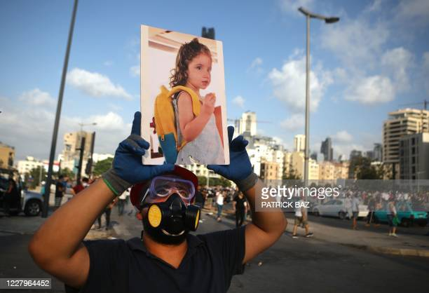 Lebanese protester carries a photo of 3-year-old Alexandra Najjar, who was wounded in the port explosion and later succumbed to her wounds, during a...