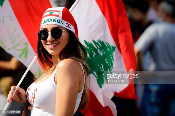 A Lebanese protester carries the national flag on the highway linking Beirut to north Lebanon in Zouk Mosbeh on October 19 a day after demonstrations...