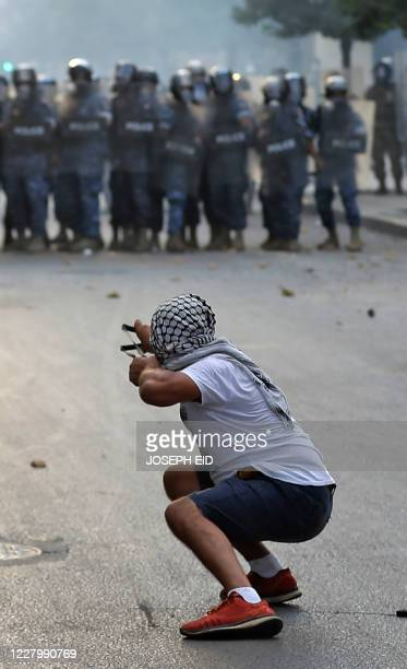 Lebanese protester, enraged by a deadly explosion, uses a slingshot to hurl stones at security forces amid clashes in central Beirut on August 10,...