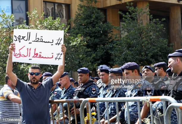 A Lebanese protester holds a placard reading in Arabic Down with the regime down with the government during a demonstration in central Beirut's...