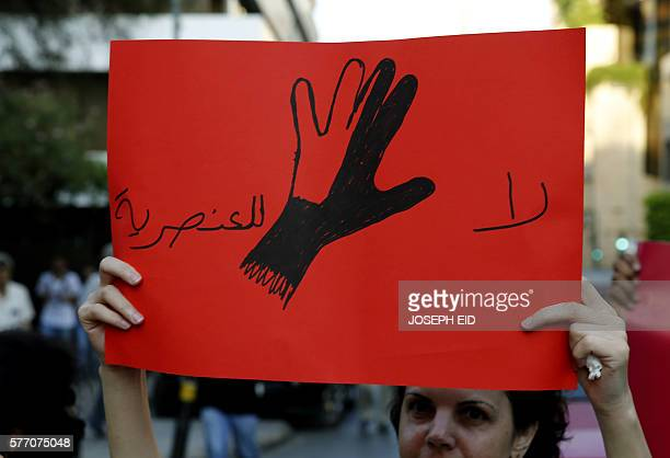 A Lebanese protester holds a placard reading in Arabic No to racism on July 18 2016 in the capital Beirut during a demonstration against racism and...