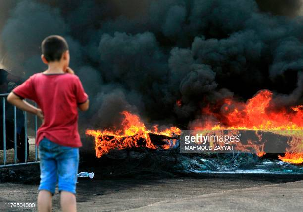 A Lebanese protester looks at a tire fire that is blocking a road in the southern Lebanese town of Adloun on October 18 during a protest against dire...