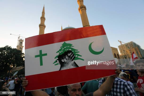A Lebanese protester raises a placard during a mass rally against a political class seen as corrupt and incapable of providing basic services on...
