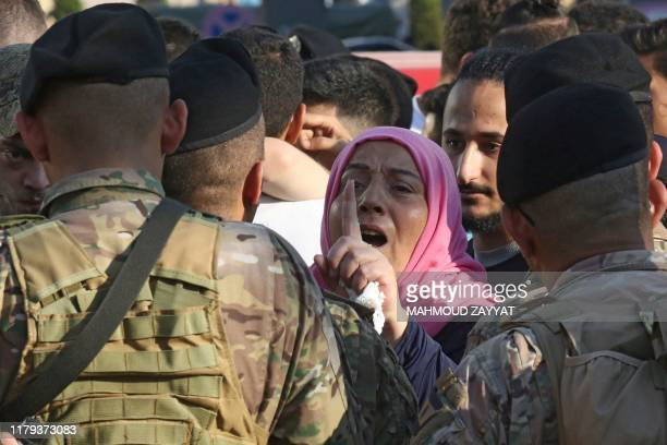 A Lebanese protester shouts slogans in front of army soldiers during ongoing antigovernment demonstrations in Lebanon's southern city of Sidon on...