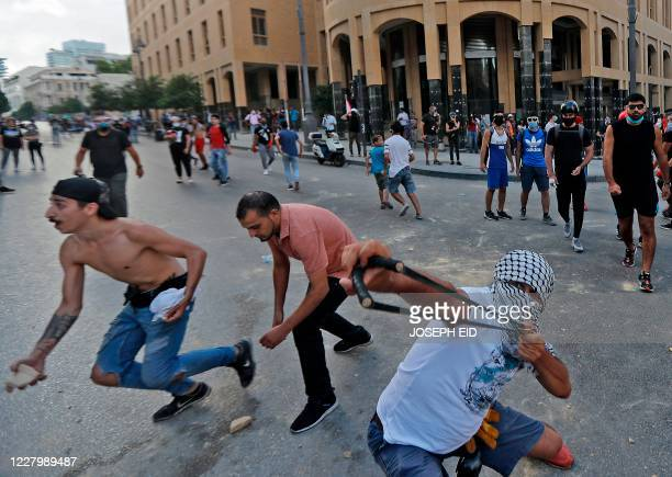 Lebanese protester uses a slingshot to hurl stones at security forces amid clashes in the vicinity of the parliament in central Beirut on August 10...