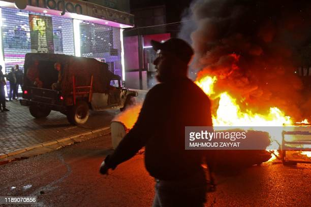 A Lebanese protester walks past a dumpster and tire fire blocking a road near an army vehicle and soldiers in the southern city of Sidon early on...