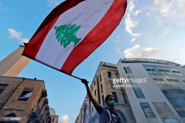 Lebanese protester waves a national flag amid clashes with security forces in central Beirut on August 10, 2020. - Lebanese Prime Minister Hassan...