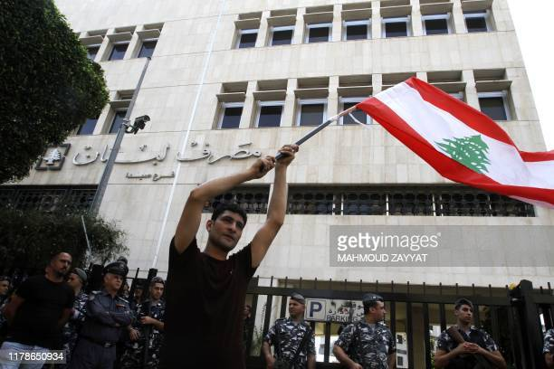 A Lebanese protester waves a national flag as he takes part an antigovernment demonstration in front of the central bank building in the southern...