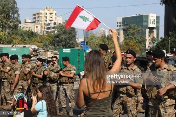 A Lebanese protester waves a national flag as soldiers stand guard on a main road on the eastern outskirts of the capital Beirut on October 22 2019...