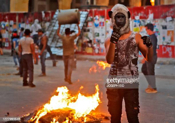 Lebanese protester, wearing a monkey mask, gestures next to burning fire amid clashes with security forces in the vicinity of the parliament in...