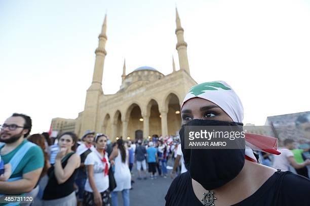 A Lebanese protester wears a mask and a national flag on her head during a mass rally against a political class seen as corrupt and incapable of...