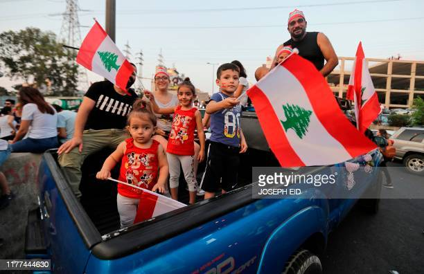 Lebanese protesters and children take to the streets during demonstrations to demand better living conditions and the ouster of a cast of politicians...