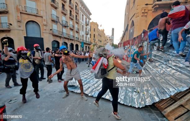 Lebanese protesters, enraged by a deadly explosion, clash with security forces in the vicinity of the parliament in central Beirut on August 10,...