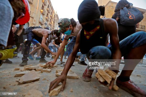 Lebanese protesters, enraged by a deadly explosion, collect stones amid clashes with security forces in the vicinity of the parliament in central...