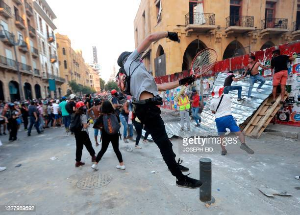 Lebanese protesters, enraged by a deadly explosion, hurl stones at security forces amid clashes in the vicinity of the parliament in central Beirut...