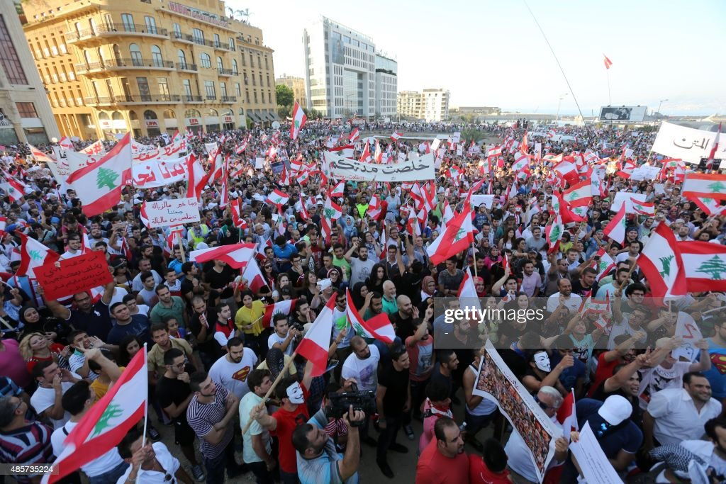 Lebanese protesters hold banners and national flags during a mass rally against a political class seen as corrupt and incapable of providing basic services on August 29, 2015 at the iconic Martyrs Square in Beirut. Waving Lebanese flags, some marked 'We've had enough', men, women and children gathered at the square which sat on a Christian-Muslim dividing line during Lebanon's 1975-1990 civil war.