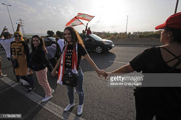 Lebanese protesters hold hands to form a human chain along the coast from north to south as a symbol of unity during ongoing antigovernment...