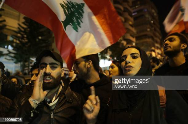 Lebanese protesters shout slogans as they gather outside the house of Lebanon's new prime minister in the capital Beirut, calling for his resignation...