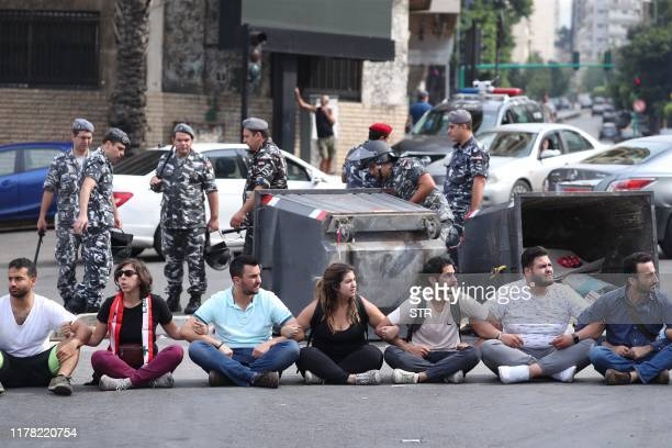 Lebanese protesters sit on the ground forming a human chain as they block a major bridge in the centre of the capital Beirut during an antigovernment...