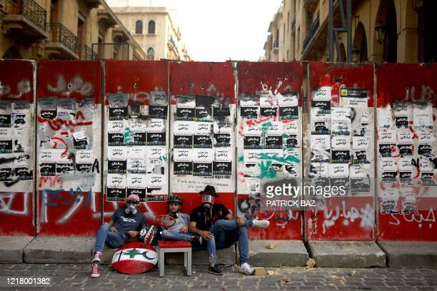 Lebanese protesters sit outside a fortified entrance of the Lebanese parliament during a demonstration in central Beirut on June 6, 2020. -...