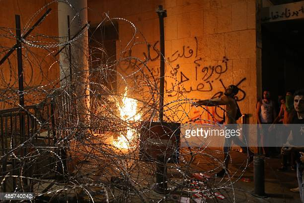 Lebanese protesters stand in front of a row of barbed wire separating them from the governmental palace as they are trying to get through it at the...