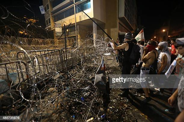 Lebanese protesters stand in front of the barbed wire separating them from the governmental palace during a mass rally against a political class seen...