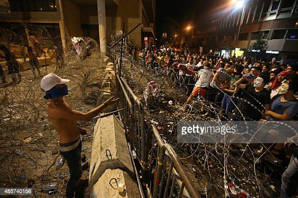 Lebanese protesters stand on both sides of the barbed wire separating them from the governmental palace as some of them managed to get through them...