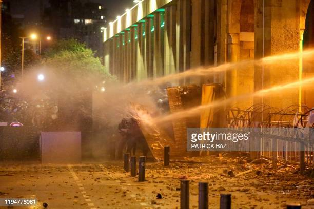 TOPSHOT Lebanese protesters take cover as riot police spray them with water from behind a barricaded road leading to parliament in central Beirut on...