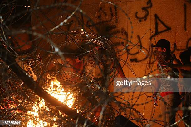 Lebanese protesters try to cross the barbed wire separating them from the governmental palace at the end of a mass rally against a political class...