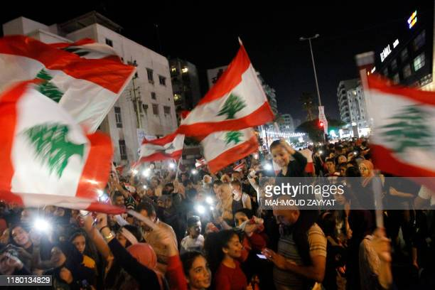 TOPSHOT Lebanese protesters use the lights of their mobile phones as they wave national flags and chant slogans during ongoing antigovernment...