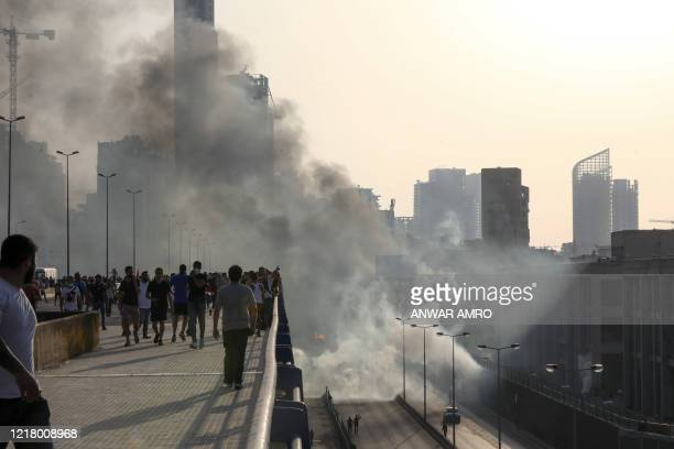 Lebanese protesters walk away from tear gas fired by riot police amid clashes following a demonstration in central Beirut on June 6, 2020. -...