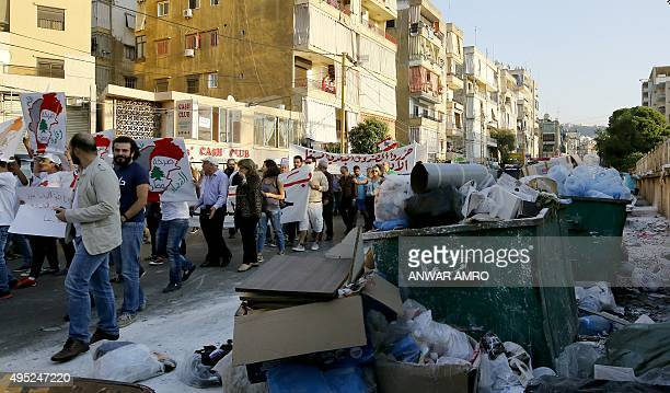 Lebanese protesters walk past piles of garbage during a demonstration organised by civil society groups to protest against the country's ongoing...