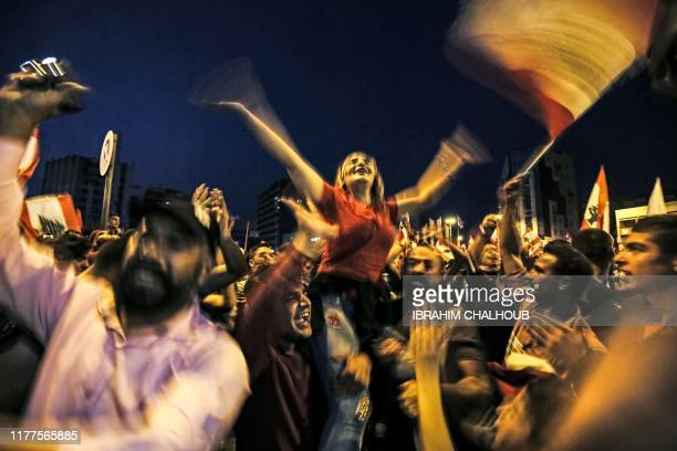 TOPSHOT Lebanese protesters wave national flags as they attend a demonstration on the sixth day of protest against tax increases and official...