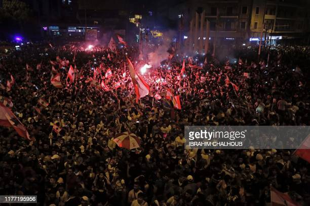 Lebanese protesters wave national flags as they take part in a rally in the northern city of Tripoli during the fourth day of demonstrations against...