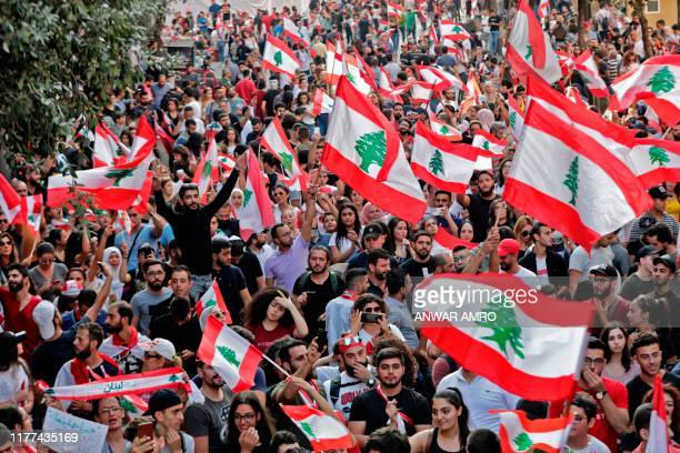 Lebanese protesters wave national flags during demonstrations to demand better living conditions and the ouster of a cast of politicians who have...