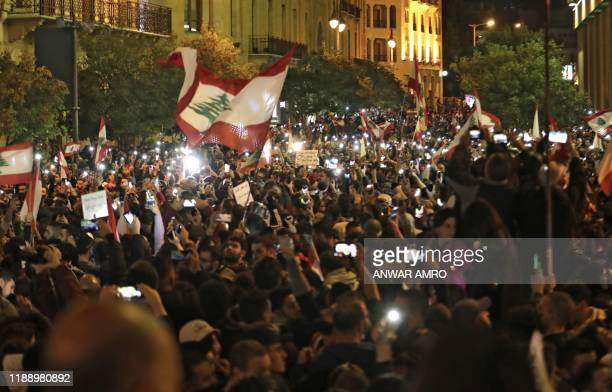 Lebanese protesters wave the national flag as they take part in an antigovernment demonstration in the downtown area of the capital Beirut on...