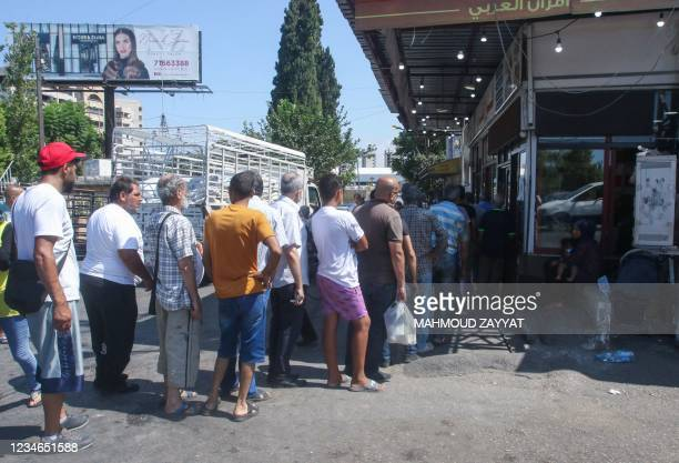 Lebanese queue for bread in front of a bakery in the southern coastal city of Sidon, on August 13 amidst a deepening economic crisis sparking various...