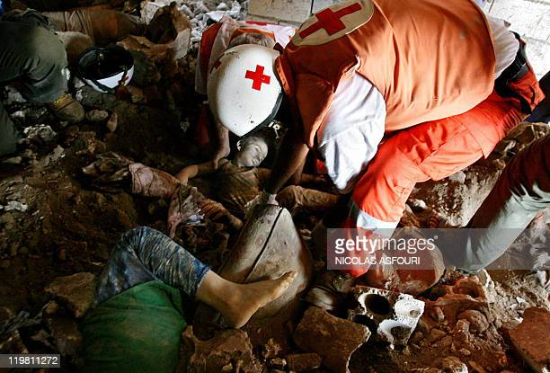 A Lebanese Red Cross rescue worker pulls the body of a girl out of the rubble of a house after Israeli air strikes on the southern village of Qana 30...