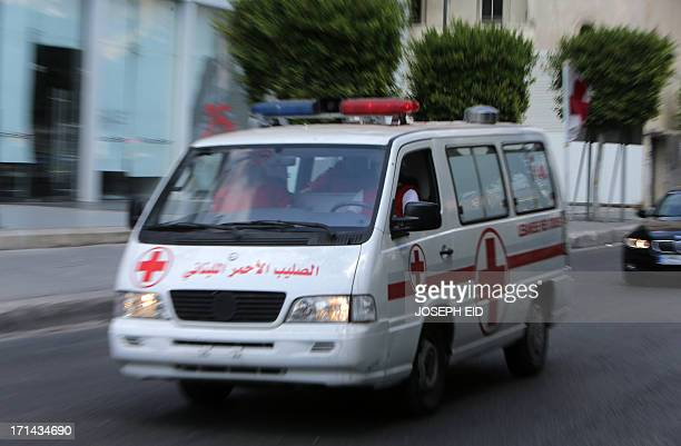 A Lebanese red cross vehicle transports wounded victims to the hospital after they were injured in the area of clashes in the Abra district of the...