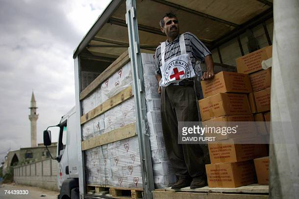 Lebanese Red Cross worker stands on a transport truck loaded with food and water to be for distributed in the Nahr alBared Palestinian refugee camp...