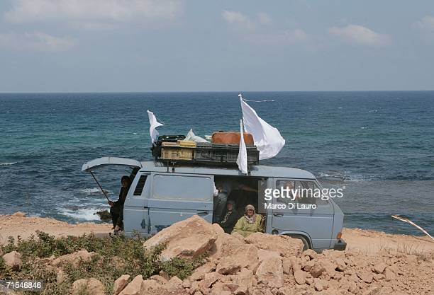 Lebanese refugees fleeing in a van display white flags as they the drive toward Tyre July 31 2006 on the road from Bint Jbail southern Lebanon The...