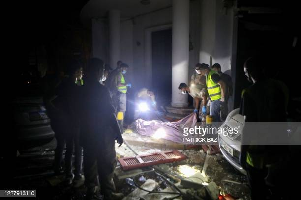 Lebanese rescue workers cover the body of a dead man following an explosion at the port of Beirut on August 4, 2020. - Two enormous explosions rocked...