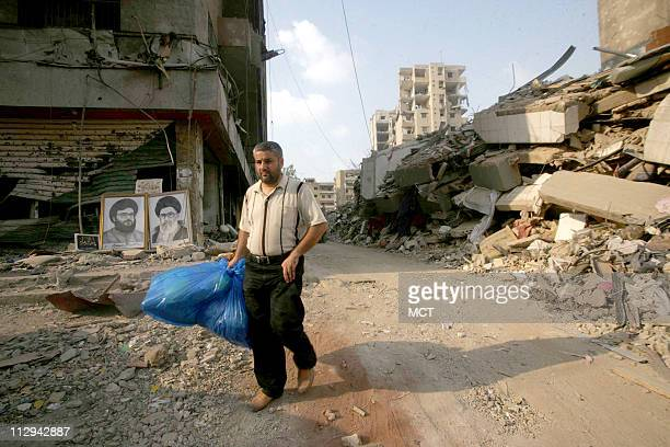 Lebanese residents walk through the rubble of buildings destroyed during the month-long Israeli offensive in Beirut's southern suburbs of Haret Hreik...