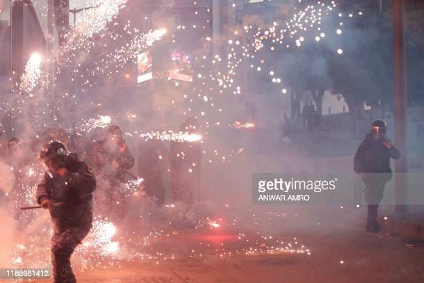 TOPSHOT Lebanese riot police react to fireworks thrown by supporters of Lebanon's Shiite Hezbollah and Amal groups during clashes on December 14 2019...